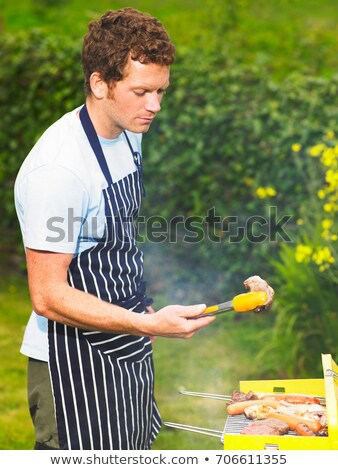 Man inspecting lamb chop at barbecue Stock photo © IS2