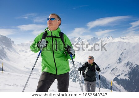 woman walking up mountain with skis Stock photo © IS2