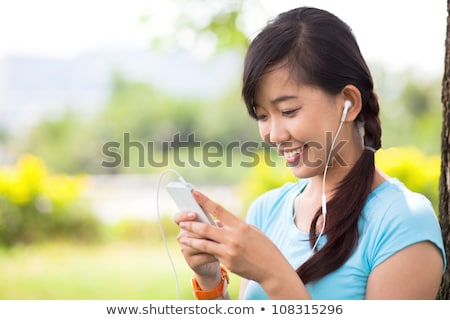 smiling girl listens to mp3 player Stock photo © IS2