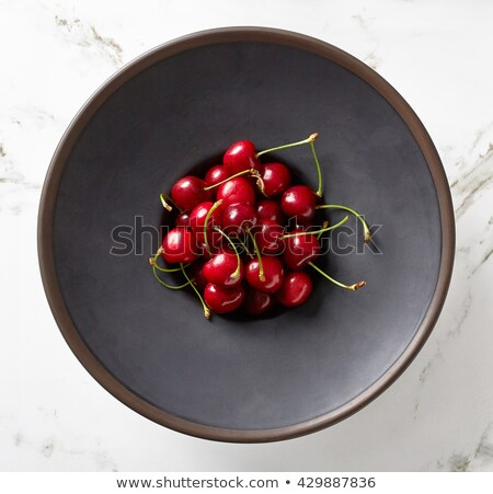 Ripe cherries in a clay bowl on black background Stock photo © vlad_star