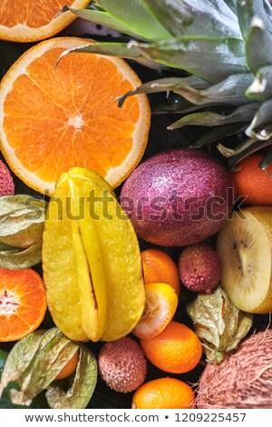 Fresh juicy tropical fruits as a backgraund. Carambola, litchi, kumquat, orange halves, phisalis on  Stock photo © artjazz
