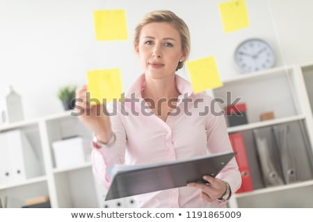 A young blonde girl stands in the office next to a transparent board with stickers and holds documen Stock photo © Traimak