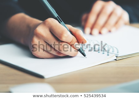 close up of a writer hands writing on a laptop on a desk stock photo © minervastock