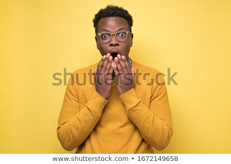 Portrait of an astonished young african man Stock photo © deandrobot