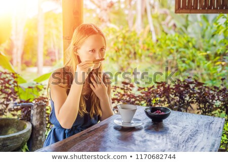 Young woman drinks coffee Luwak in the gazebo with sunlight Stock photo © galitskaya