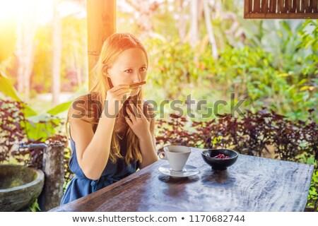 Young woman drinks coffee Luwak in the gazebo with sunlight stock photo © galitskaya