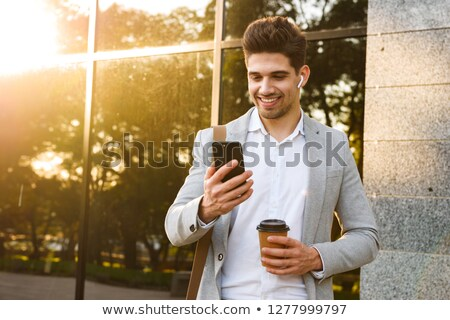 Photo of businesslike guy in suit holding mobile phone, while st Stock photo © deandrobot