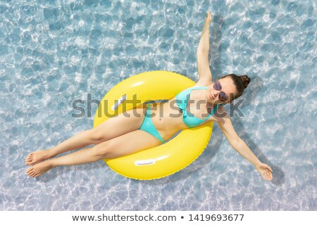 Young Woman Floating On Yellow Float On Shallow Sea Water Stock photo © AndreyPopov