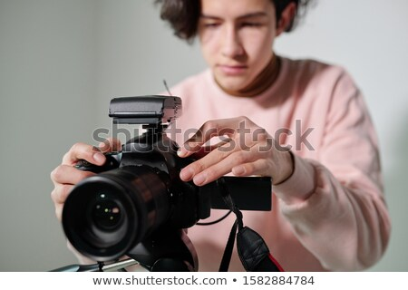 Hands of young cameraman in powdery pink sweatshirt regulating video equipment Stock photo © pressmaster