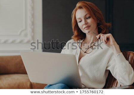 Concentrated serious redhead woman makes remote job indoors, sits in comfortable armchair, holds tra Stock photo © vkstudio