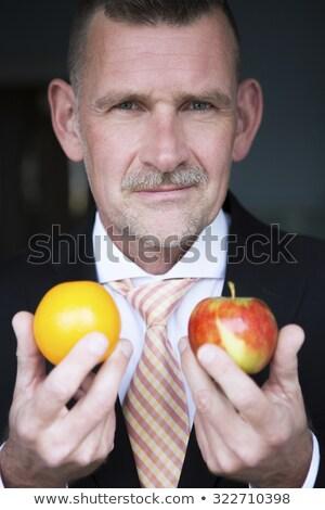Stock photo: Caucasian businessman comparing apple to orange