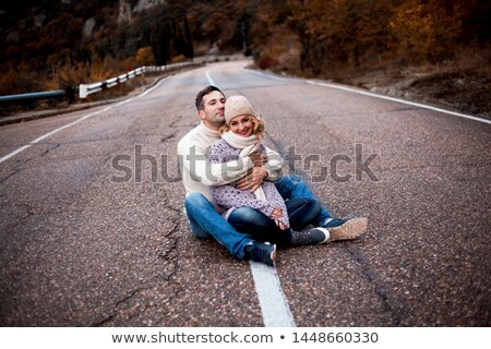 Férfi tart barátnő kezek ül kint Stock fotó © deandrobot