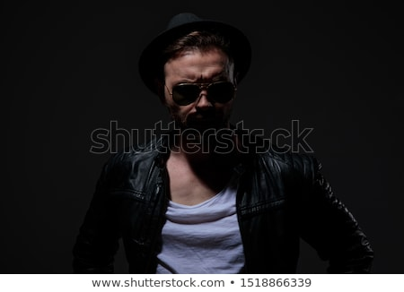 arrogant young fashion man in leather jacket and sunglasses posi Stock photo © feedough
