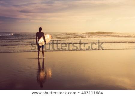 Uomo tavola da surf piedi spiaggia guardando orizzonte Foto d'archivio © deandrobot