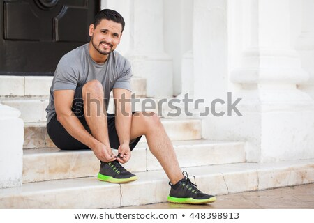 Young bearded sports man athlete ties his shoelaces outdoors Stock photo © deandrobot