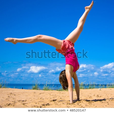 Athletic girl stands upside down in gym Stock photo © bezikus