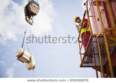 Worker directing crane on oil rig Stock photo © IS2
