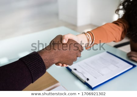 A Middle Eastern businessman and woman shaking hands stock photo © monkey_business