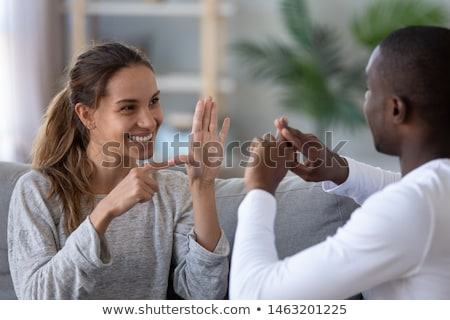 Casal linguagem gestual sorridente sessão Foto stock © AndreyPopov