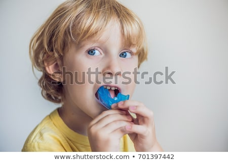 Three-year old boy shows myofunctional trainer. Helps equalize the growing teeth and correct bite, d Stock photo © galitskaya