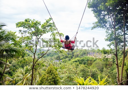Young tourist woman swinging over the tropical rainforest at Bal Stock photo © boggy