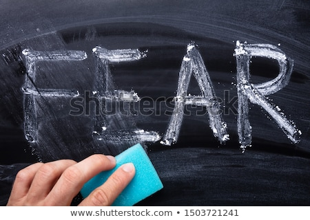 Man's Hand Erasing Fear Word With Blue Sponge Stock photo © AndreyPopov