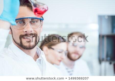 Analytical Chemist analyzing a red solution Stock photo © Kzenon