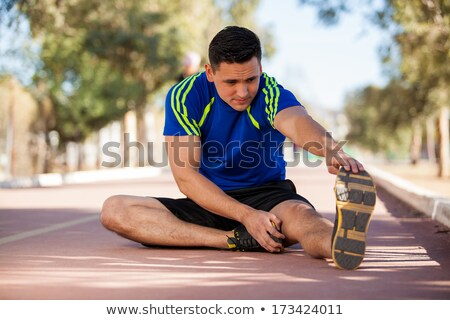Athlete man doing some stretching exercises legs before running  Stock photo © Freedomz