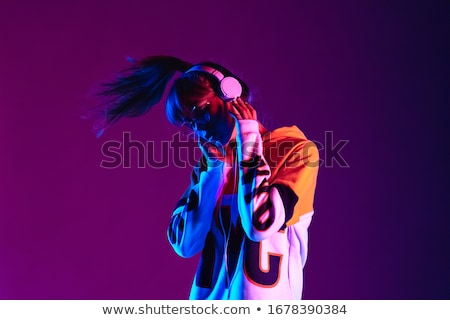 Pretty happy girl listening to music with earphones. Stock photo © lichtmeister