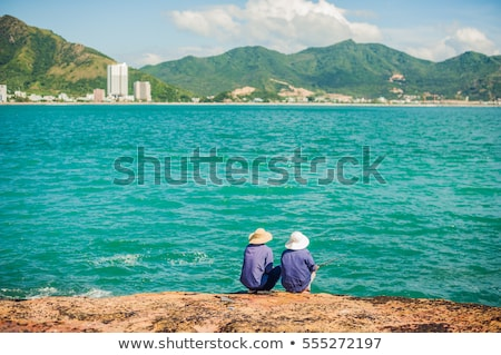 Vietnamese fishermen sitting on the edge of a cliff and fishing. Stock photo © galitskaya