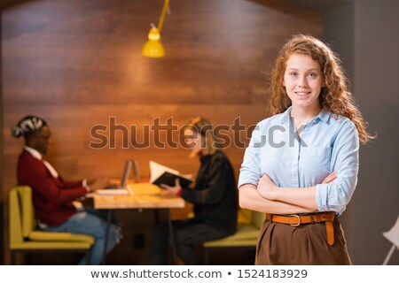 Happy cross-armed girl in casualwear and her two groupmates on background Stock photo © pressmaster