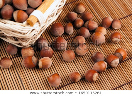 whole hazelnut kernels in a wicker basket on a bamboo napkin Stock photo © mizar_21984