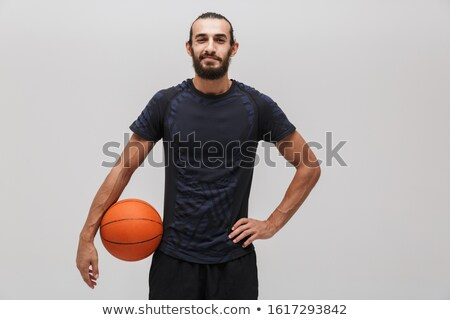 Image of young pleased man posing with basketball and smiling Stock photo © deandrobot