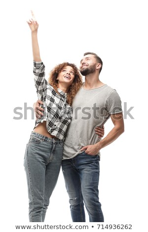 Attractive girl posing in style and pointing upwards Stock photo © stockyimages