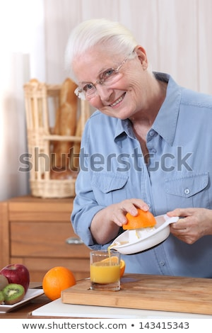 Stock photo: Elderly woman pouring freshly squeezed orange juice