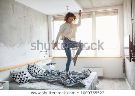 Feliz mujer jeans cama mujer sonriente Foto stock © wavebreak_media