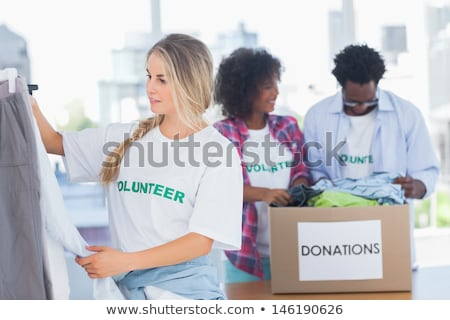 Woman sorting clothes on rail and smiling Stock photo © wavebreak_media