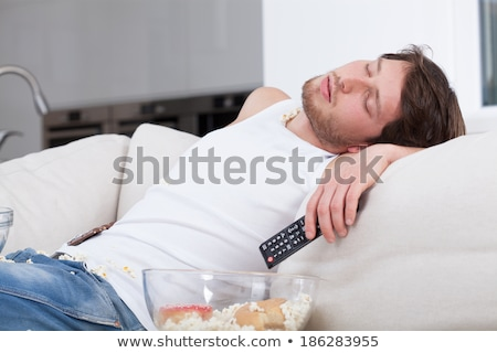 Couch potato sleeping in front of tv Stock photo © curvabezier