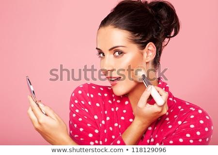 laughing beautiful woman applying blusher stock photo © dash