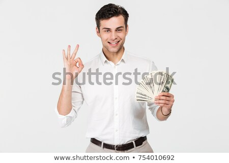 businessman holding money and showing ok stock photo © orensila