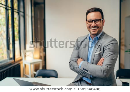 Handsome businessman in formal wear looking at camera Stock photo © deandrobot