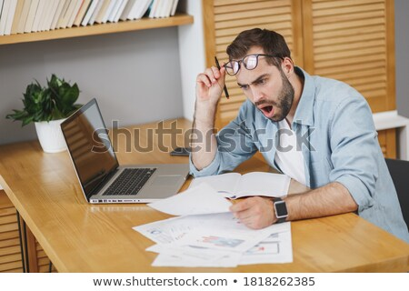 Dissatisfied young businessman in glasses looking at camera Stock photo © deandrobot