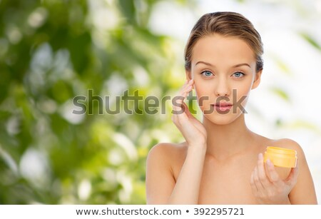 young woman applying cream to her face over green stock photo © dolgachov
