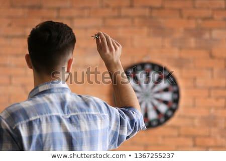 Caucasian man playing darts. Stock photo © iofoto