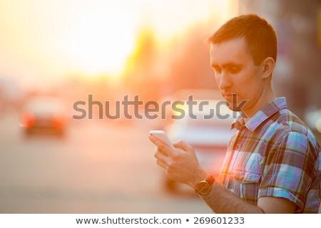 Man using mobile phone on street in sunset Stock photo © stevanovicigor