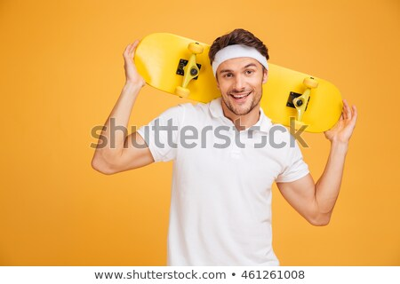 Young skateboarder man holding skateboard on his shoulders Stock photo © deandrobot