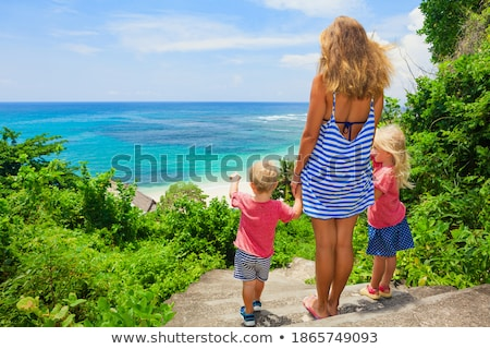 Mother and son go to the sea beach. Resort vacation on tropical beach. Path to beach Stock photo © galitskaya