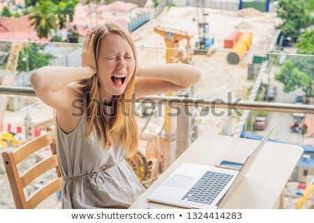 The girl works in a noise on the background of construction. Work in the noise concept Stock photo © galitskaya