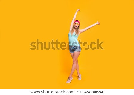 Full-size portrait of young blondy girl in a pink stand holding her hands up isolated on bright yell Stock photo © ElenaBatkova