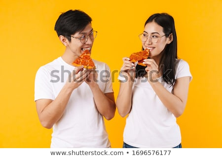 portrait of a laughing young asian man eating pizza stock photo © deandrobot